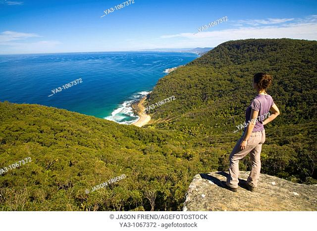 Australia, New South Wales, Royal National Park  Female hiker walking the coastal path takes a break to look down on Werrong Beach from a rocky lookout above