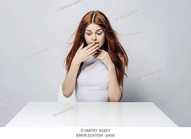 Surprised Caucasian woman sitting at windy table
