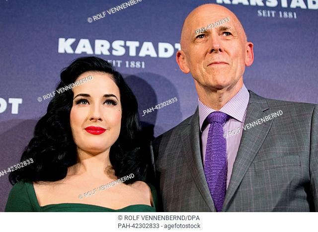 The CEO of the warehouse chain Karstadt, Andrew Jennings (R) and burlesque model Dita von Teese pose for the camera within a newly renovated Karstadt shop in...