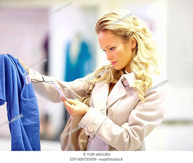 Pretty young woman checking a sales tag