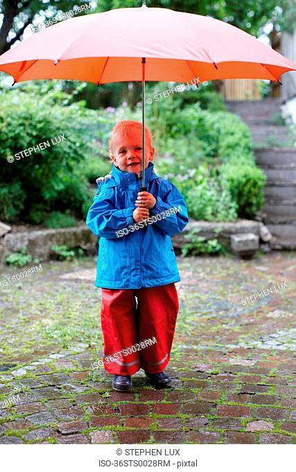Toddler boy holding umbrella in backyard