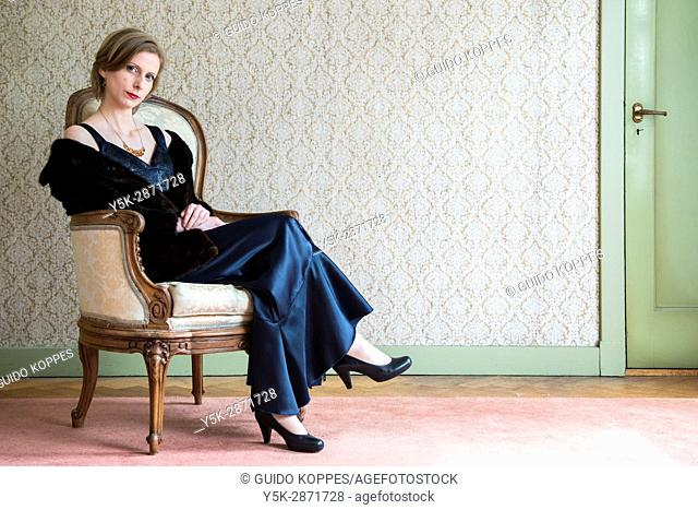Tilburg, Nederland, Adult caucasian woman wearing evening dress, while sitting in a chair and getting ready to go out to a classical concert