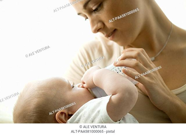 Mother feeding infant with baby bottle