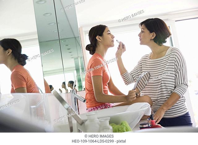 Mother applying lipstick to daughter in bathroom