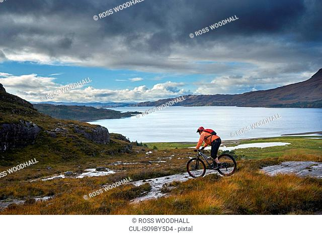 Male mountain biker biking down toward loch in mountain landscape, Achnasheen, Scottish Highlands, Scotland