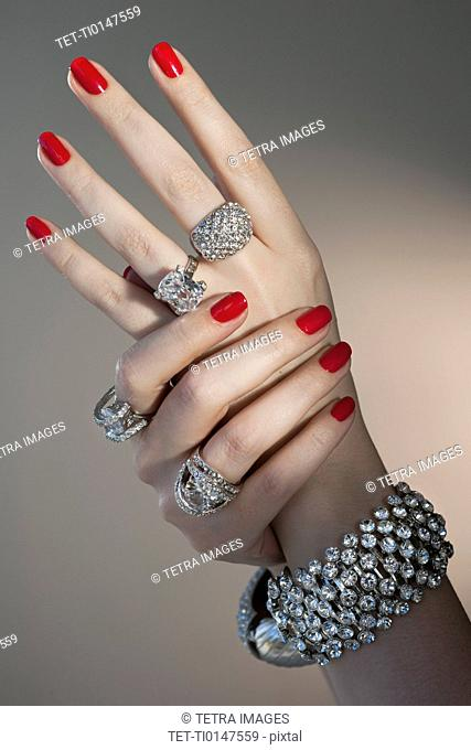 Close up of woman's hands with red nail polish and diamond jewelry