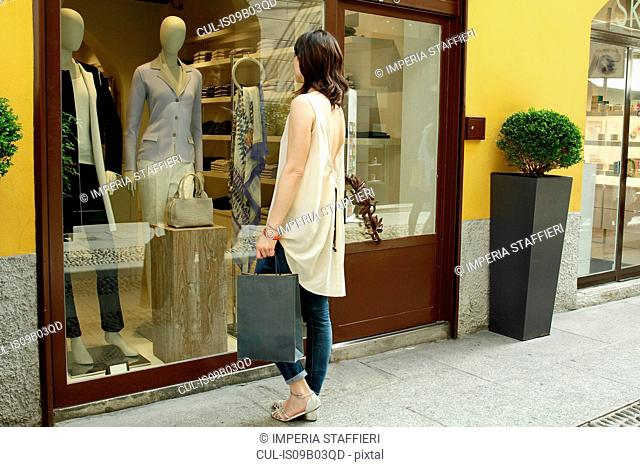 Female shopper looking in boutique window, Milan, Italy