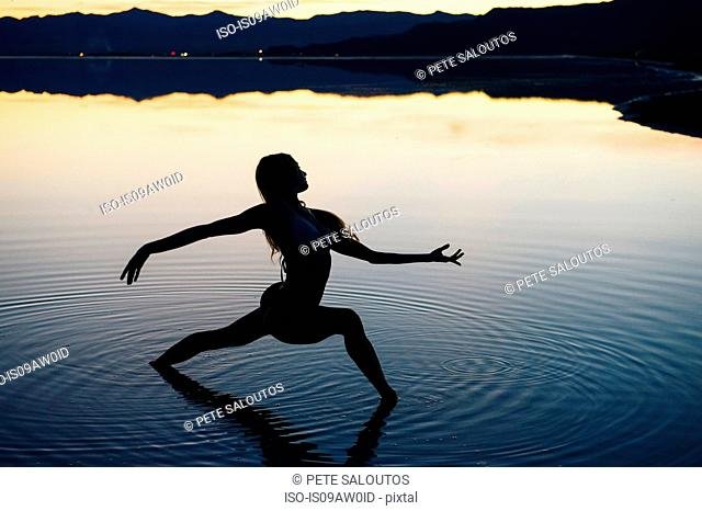 Silhouetted female dancer poised with open arms in lake at sunset, Bonneville Salt Flats, Utah, USA