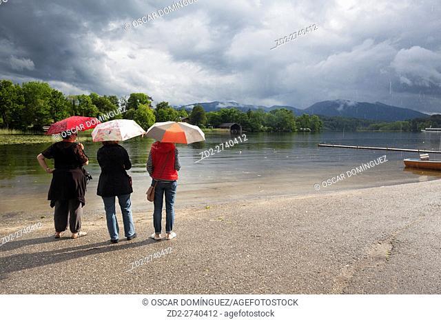 Rear view of three women sheltering under a umbrella. Staffelsee. Upper Bavaria. Germany