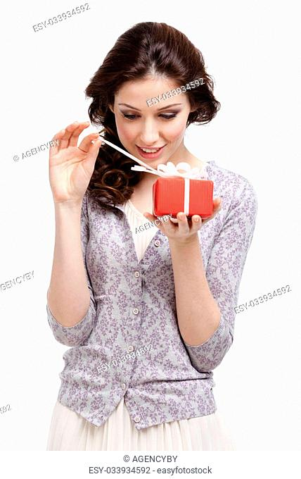 Young lady opens her present wrapped in red paper, isolated on white