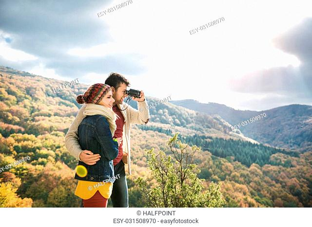 Beautiful young couple on a walk in sunny autumn forest, man looking through binoculars