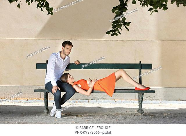 Couple on a bench in a garden, Terrasse De l'Orangerie, Jardin des Tuileries, Paris, Ile-de-France, France