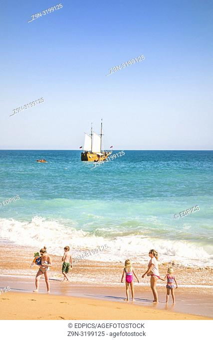 families at benagil beach with coast tour masted vessel in background, benagil, algarve, portugal