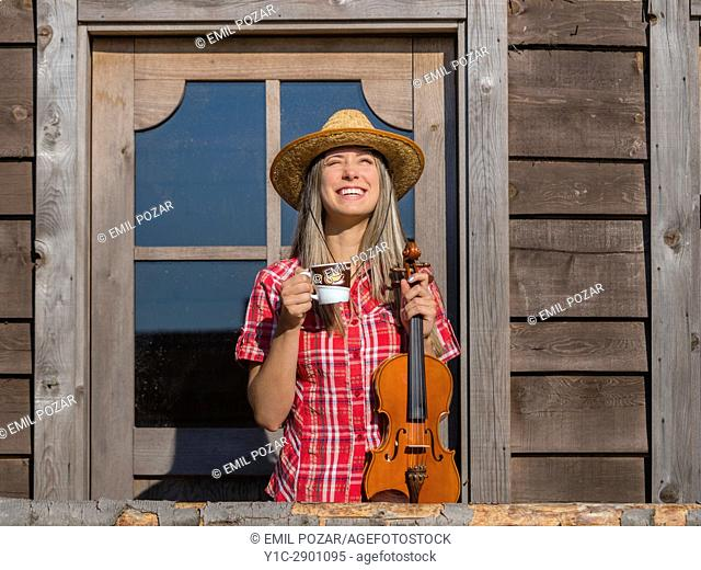 Attractive Country-girl with cup of coffee cappuccino and violin in hands laughing standing front frontal view in wild west environment. Croatia