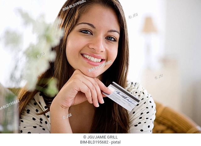 Smiling Indian woman holding credit card