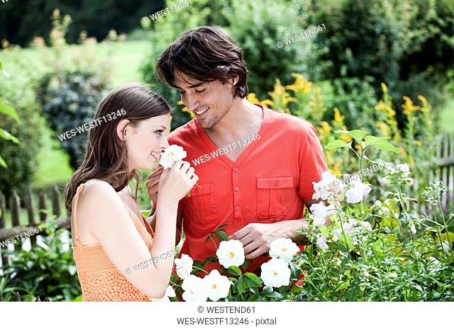 Germany, Bavaria, Couple in the garden, woman smelling flower, smiling, portrait