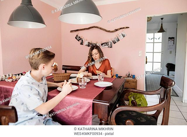 Mother and son sitting at dining table at home