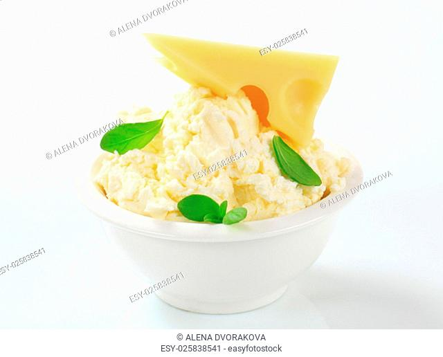 white creamy cheese and a piece of emmentaler in a porcelain bowl
