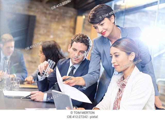 Business people with paperwork and digital tablet in conference room
