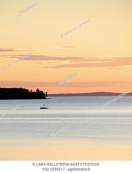 Tranquil scene of people in small steamboat at sunset. Lake VŠttern, Sweden