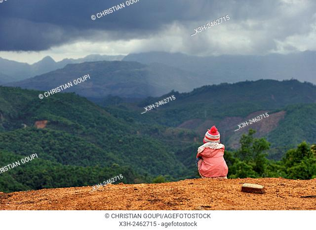 sitting child admiring landscape at a mountain pass on the road 13, around Udomxay, Oudomxay Province in northwestern Laos, Southeast Asia