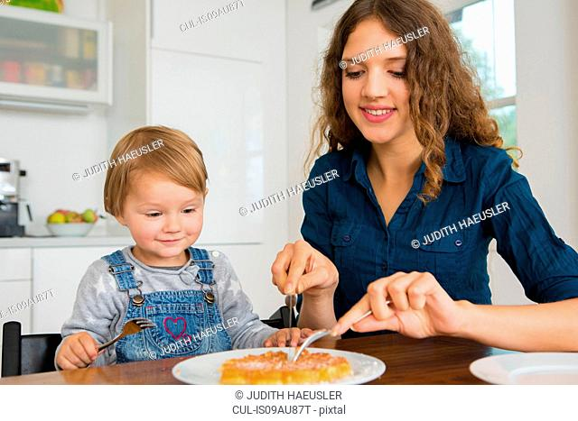 Teenage girl cutting cake for female toddler at kitchen table