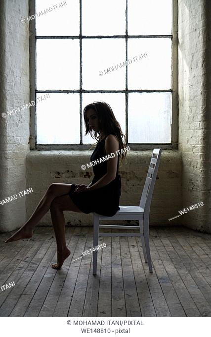 Sad woman sat on a chair by the window