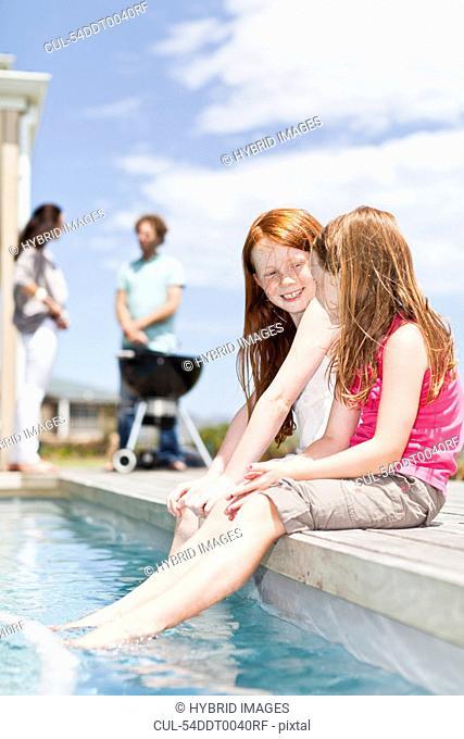 Girls dangling feet in swimming pool