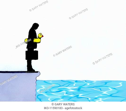 Businessman with inflatable ring looking down at water