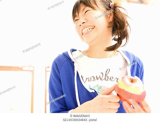 A woman striping an apple