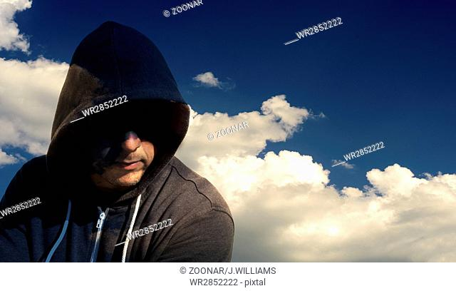 Single masked computer hacker thief with a cloud background for internet security based concepts