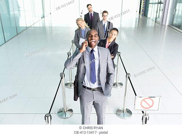Businessman talking on cell phone in line
