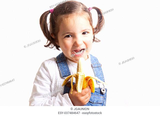 Portrait of happy girl holding a banana. Isolated over white background