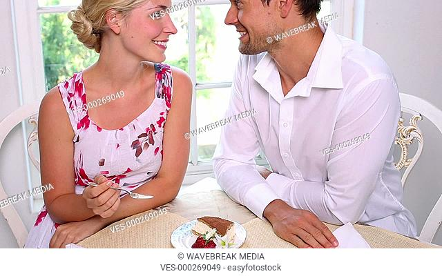 Happy young couple eating cake together