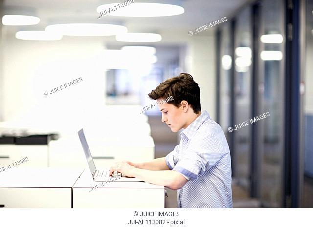 Teenage boy using laptop in office