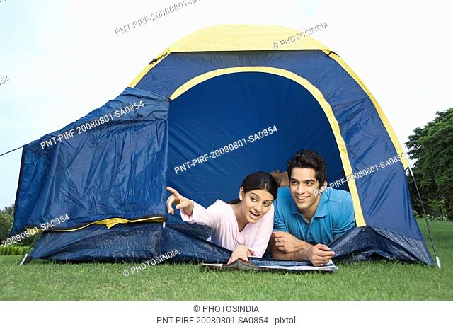 Woman pointing forward with a man from a tent