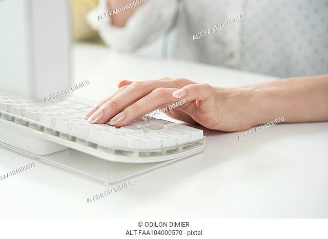 Woman typing on computer keyboard, cropped