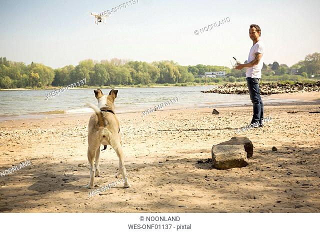 Man with a dog flying drone at a river