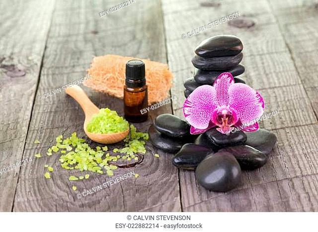 Orchid, bath salt, essential oil and black stones close-up