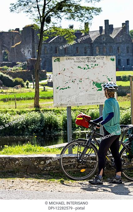 Female cyclist looking at a large map sign along a canal with an Abbey in the background; Saint-Gelven, Brittany, France