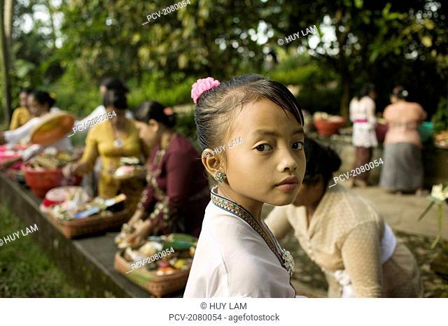 Young girl preparing for Kuningan Festival; Bali, Indonesia