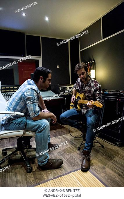 Guitar player talking to man in a recording studio