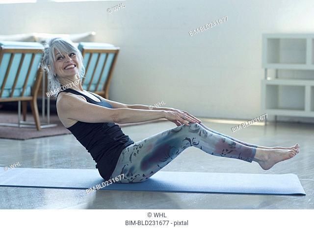 Woman doing yoga balancing on exercise mat