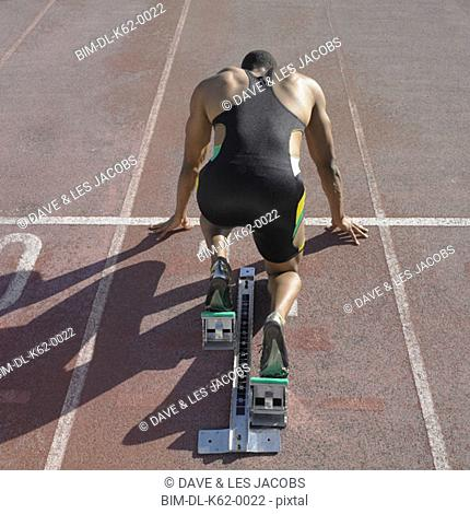African male athlete in starting position on track, Perth, Australia