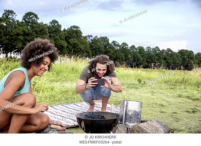 Smiling young man with girlfriend taking a picture of barbecue grill in the nature