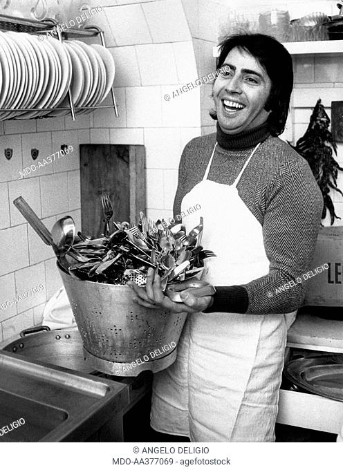 Lando Fiorini in the kitchen. Italian singer and actor Lando Fiorini (Leopoldo Fiorini) in the kitchen holding a colander full of cutlery. Rome, 1970s