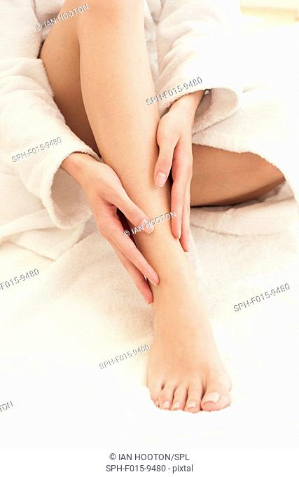 MODEL RELEASED. Young woman rubbing ankle