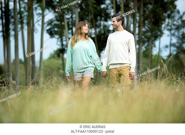 Young couple walking hand in hand through tall grass