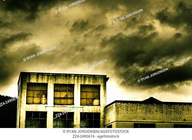 Storm clouds gather over a grungy abandoned darparted store. Tension building