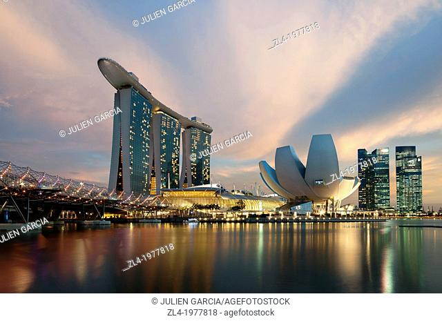 Marina Bay Sands hotel at sunset with the ArtScience museum designed by the architect Moshe Safdie, the helix bridge on the left